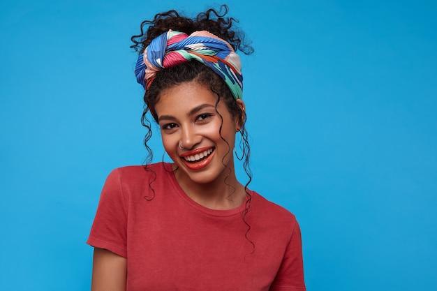 Belle jeune femme bouclée aux cheveux assez sombre avec une coiffure décontractée à la recherche de plaisir à l'avant et souriant largement en se tenant debout sur le mur bleu