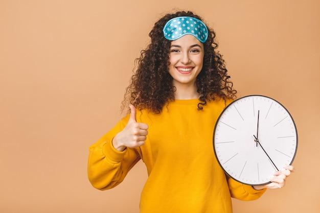 Belle jeune femme bouclée posant sur fond beige avec horloge et masque de sommeil. pouces vers le haut.
