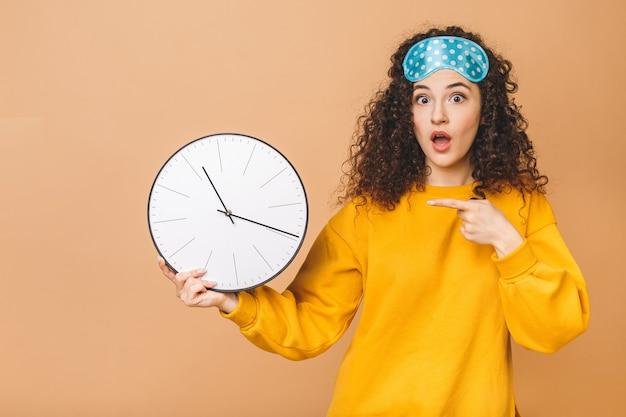 Belle jeune femme bouclée posant sur fond beige avec horloge et masque de sommeil.