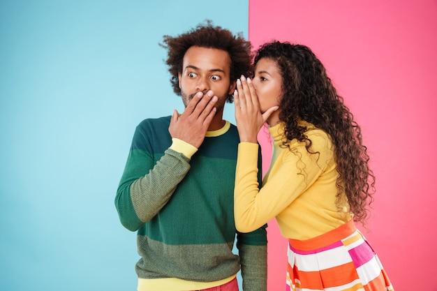 Belle jeune femme bouclée racontant des secrets à son petit ami