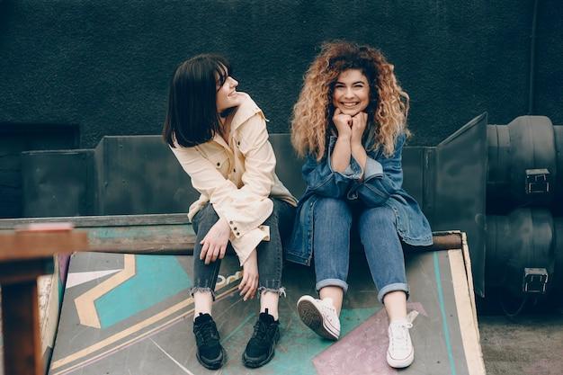 Belle jeune femme bouclée vêtue de jeans regardant la caméra en riant pendant que sa meilleure amie la regarde en plein air.