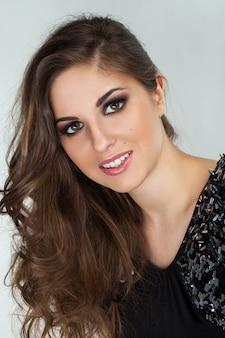 Belle jeune femme avec des boucles et du maquillage