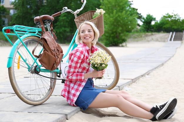 Belle jeune femme avec bouquet de fleurs assis près de vélo à l'extérieur