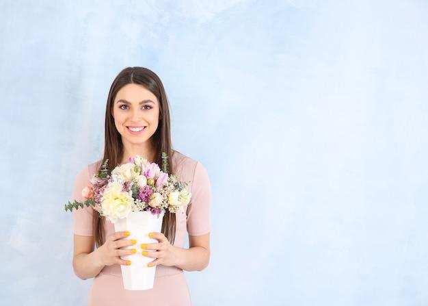 Belle jeune femme avec bouquet de fleurs sur bleu