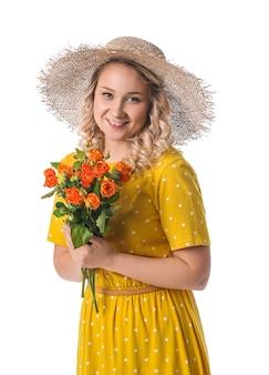 Belle jeune femme avec bouquet de fleurs sur mur blanc