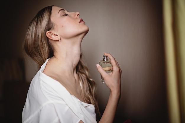 Belle jeune femme avec une bouteille de parfum