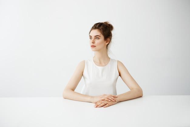 Belle jeune femme brune assise à table directement sur fond blanc.