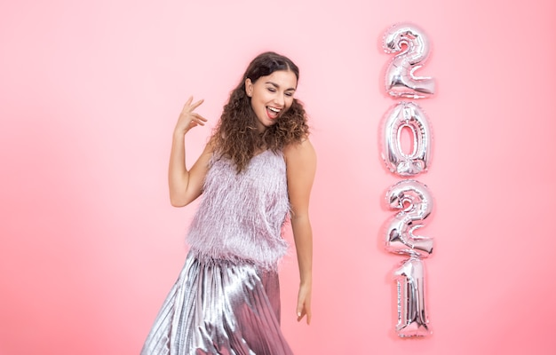 Belle jeune femme brune aux cheveux bouclés dans des vêtements de fête a l'air heureux sur un mur rose avec des ballons d'argent pour le concept de nouvel an