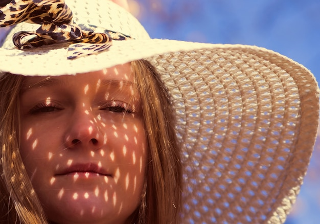 Belle jeune femme brune aux cheveux longs avec chapeau