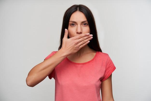 Belle jeune femme brune aux yeux bruns habillée en t-shirt rose en gardant la paume sur sa bouche tout en regardant, isolé