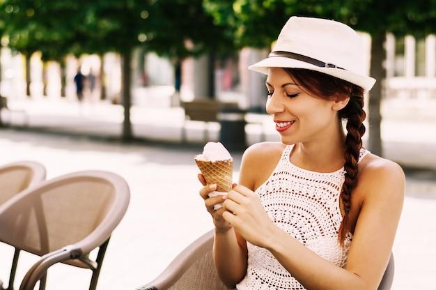 Belle jeune femme brune ayant des glaces rafraîchissantes.