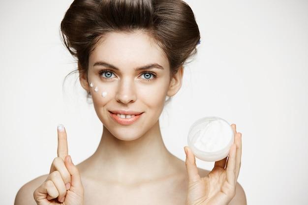 Belle jeune femme brune en bigoudis souriant visage crémeux. traitement facial. beauté santé et cosmétologie.