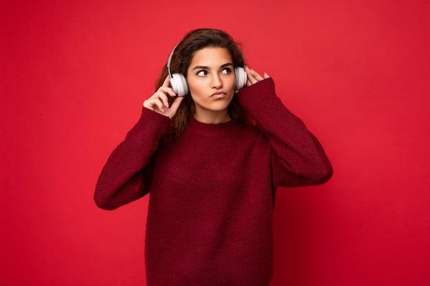 Belle jeune femme brune bouclée portant un pull rouge foncé isolé sur un mur de fond rouge portant des écouteurs bluetooth blancs écoutant de la musique et s'amusant à regarder sur le côté et à penser