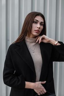 Belle jeune femme brune en chemise beige dans un élégant manteau noir avec un sac à main en cuir à la mode posant près d'un mur en métal vintage dans la rue. jolie fille à la mode. dame élégante.