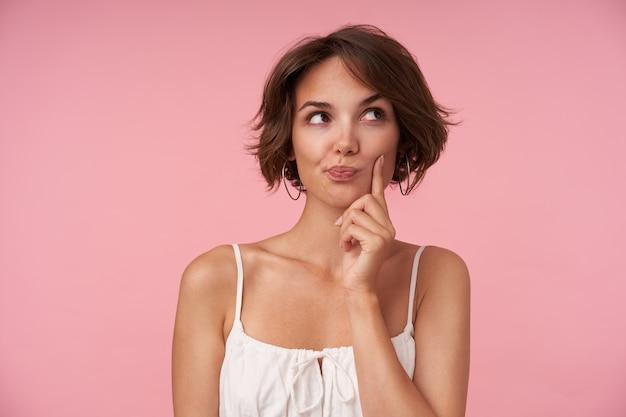 Belle jeune femme brune avec une coiffure décontractée portant un haut blanc en position debout, regardant de côté pensivement et rasant les sourcils
