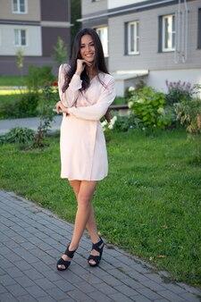 Une belle jeune femme brune dans une robe d'été légère pose à l'extérieur par une chaude journée