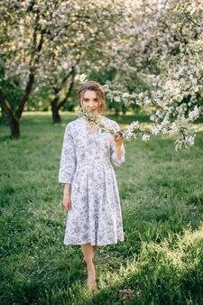 Belle jeune femme brune debout près du pommier par une chaude journée d'été