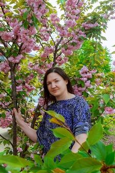 Belle jeune femme brune debout près de pommier en fleurs