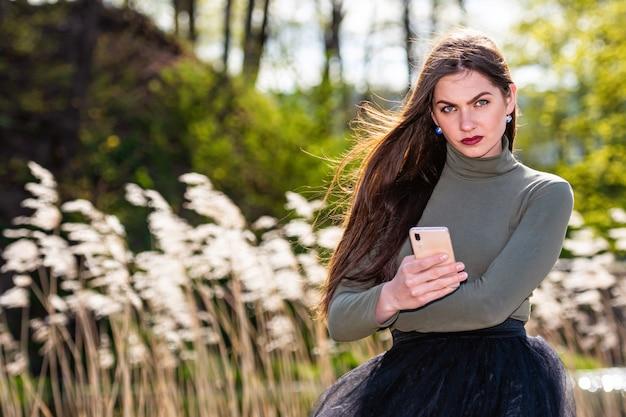 Belle jeune femme brune émotionnelle se sent triste quand elle lit le message sur le smartphone