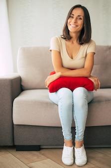 Belle jeune femme brune heureuse se détend sur le canapé à la maison et rêve