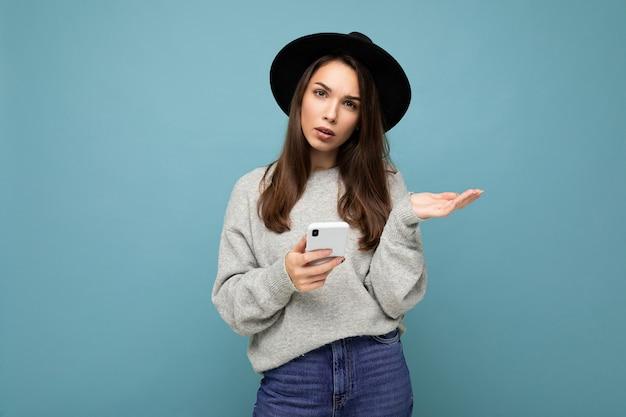 Belle jeune femme brune insatisfaite demandant un chapeau noir et un pull gris tenant