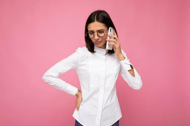 Belle jeune femme brune insatisfaite portant un chemisier blanc et des lunettes optiques debout