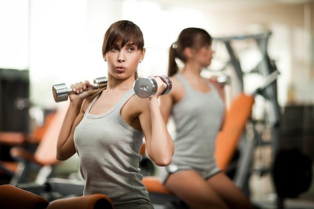 Belle jeune femme brune instructeur sportswear montrant comment utiliser des haltères à une autre fille dans la salle de gym