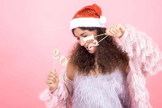 Belle jeune femme brune joyeuse aux cheveux bouclés dans un chapeau de noël sur un mur rose tenant un numéro en bois pour le concept de nouvel an