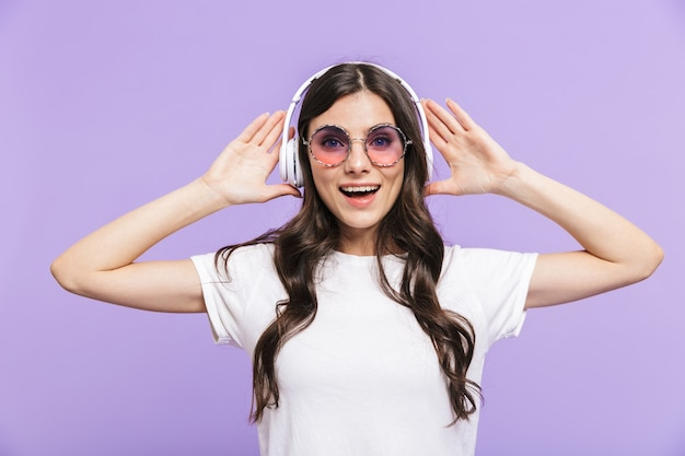 Belle jeune femme brune joyeuse debout isolée sur un mur violet, écoutant de la musique avec des écouteurs