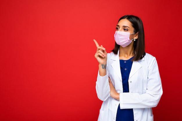 Belle jeune femme brune en masque de protection contre les virus sur le visage contre le coronavirus et blouse médicale blanche