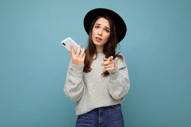 Belle jeune femme brune pensant pointer du doigt vers vous portant un chapeau noir et un pull gris tenant un smartphone regardant vers le côté des textos isolés sur fond.