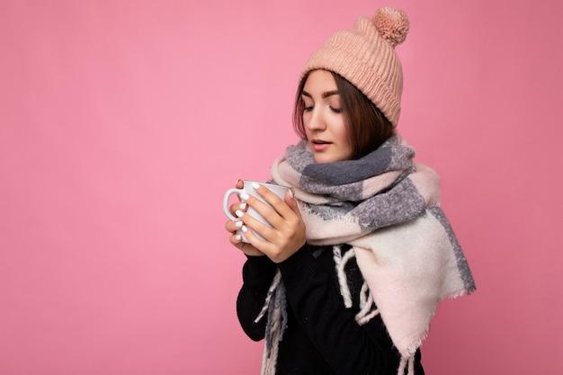 Belle jeune femme brune portant un chapeau de pull noir et une écharpe chaude isolée sur un mur rose tenant une tasse de papier buvant du thé chaud et regardant vers le bas. copie espace