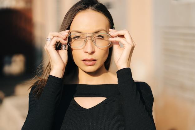 Belle jeune femme brune portant un haut noir et des lunettes transparentes posant dans la rue