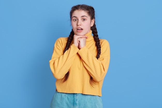 Belle jeune femme brune portant un pull jaune, a l'air choqué, gardant les poings sous le menton et la bouche ouverte, debout isolé sur mur bleu