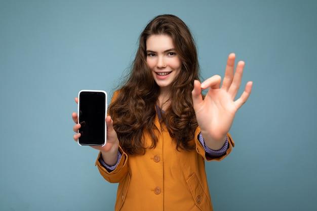 Belle jeune femme brune portant une veste orange isolée sur fond bleu tenant dans la main