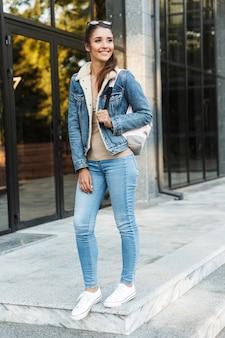 Belle jeune femme brune portant une veste, portant un sac à dos marchant à l'extérieur