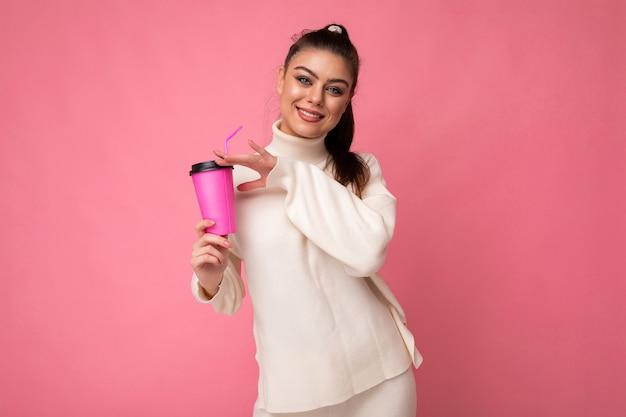 Belle jeune femme brune positive portant des vêtements élégants décontractés isolés sur un mur de fond coloré tenant une tasse de papier pour une maquette de boire du café en regardant la caméra.