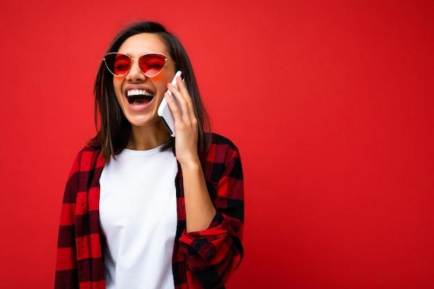 Belle jeune femme brune en riant positif portant une chemise rouge élégante, un t-shirt blanc et des lunettes de soleil rouges