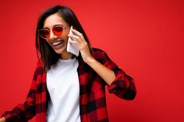 Belle jeune femme brune riante positive portant un t-shirt blanc élégant en chemise rouge et des lunettes de soleil rouges isolées sur fond rouge parlant au téléphone portable regardant vers le bas sur le côté