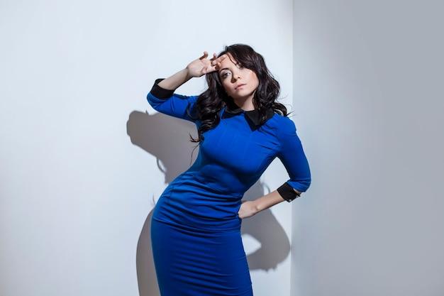 Belle jeune femme brune en robe bleue contre un mur blanc tourné avec une lumière dure et des ombres contrastées