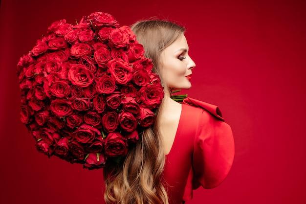 Belle jeune femme brune en rouge avec bouquet de roses rouges sur l'épaule