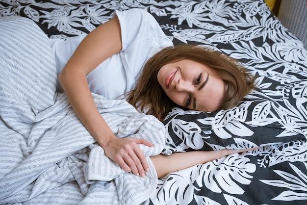 Belle jeune femme brune se réveille le matin alors qu'elle est allongée dans un lit blanc en libre-service.