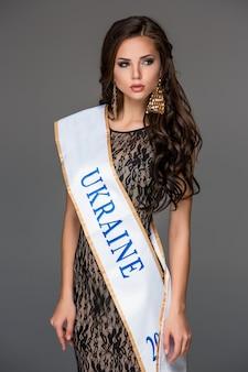 Belle jeune femme brune avec ses cheveux posant dans une robe longue ai.