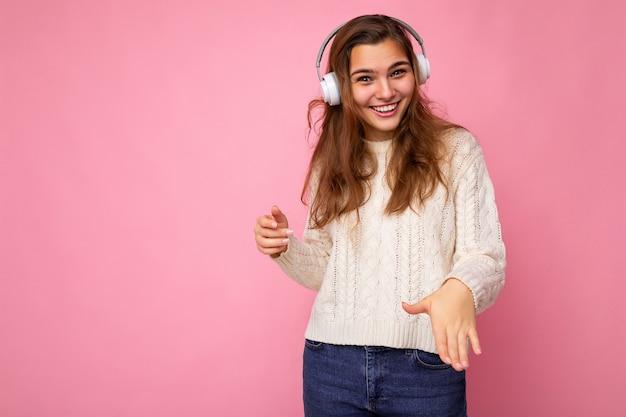 Belle jeune femme brune souriante et bouclée portant un pull blanc isolé sur un mur de fond rose portant des écouteurs bluetooth blancs écoutant de la musique cool en regardant la caméra