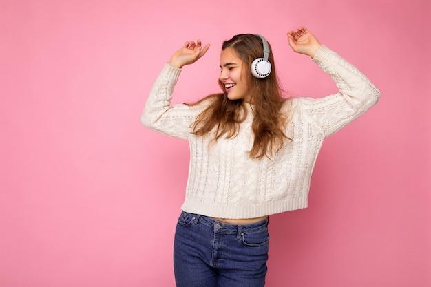 Belle jeune femme brune souriante et bouclée portant un pull blanc isolé sur un mur de fond rose portant des écouteurs bluetooth blancs écoutant de la musique cool regardant sur le côté et dansant