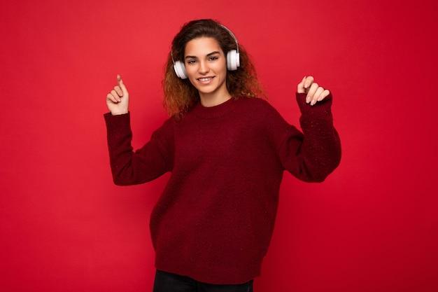 Belle jeune femme brune souriante et bouclée portant un pull rouge foncé isolé sur rouge