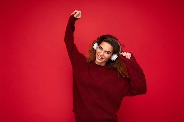 Belle jeune femme brune souriante et frisée portant un pull rouge foncé isolé sur un mur de fond rouge portant des écouteurs bluetooth blancs, écoutant de la musique et s'amusant en regardant la caméra.