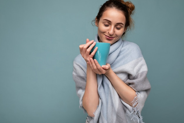 Belle jeune femme brune souriante heureuse portant un foulard bleu chaud isolé