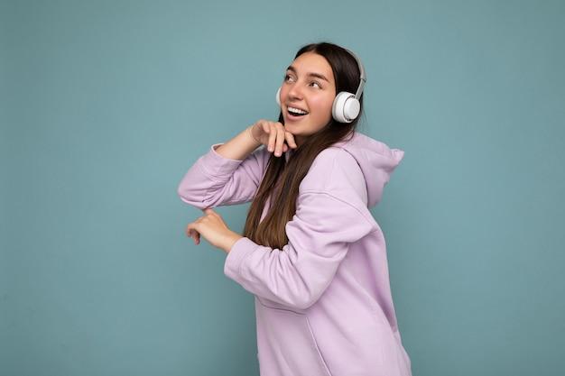 Belle jeune femme brune souriante et heureuse portant un sweat à capuche violet clair isolé sur fond bleu