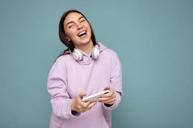 Belle jeune femme brune souriante portant un sweat à capuche violet clair isolé sur bleu